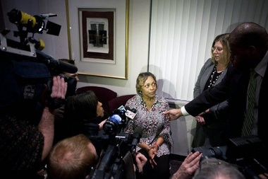 Tonya Battle talks with the media following a news conference Friday, Feb. 22, that Hurley Medical Center said it settled Battle's lawsuit that claimed she wasn't allowed to take care of a baby because she is black.