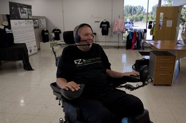 EZ Awareness By Design owner Eric Thomas smiles at his office at 501 S. Averill St. in Flint. Thomas was left paralyzed from the neck down after a stray bullet struck him in the spine. In addition to owning his own business, Thomas is a public speaker and advocate for the disabled. Michelle Tessier | MLive.com