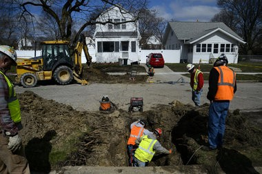 Workers from William E. Walter Inc., Fessler & Bowman Inc. and Johnson & Wood LLC work to put a new copper main service line in to replace an old lead line, as part of Mayor Karen Weaver's Fast Start initiative to replace lead-tainted service lines, on Friday, March 25, 2016 on Joliet St. in Flint. Rachel Woolf | MLive.com