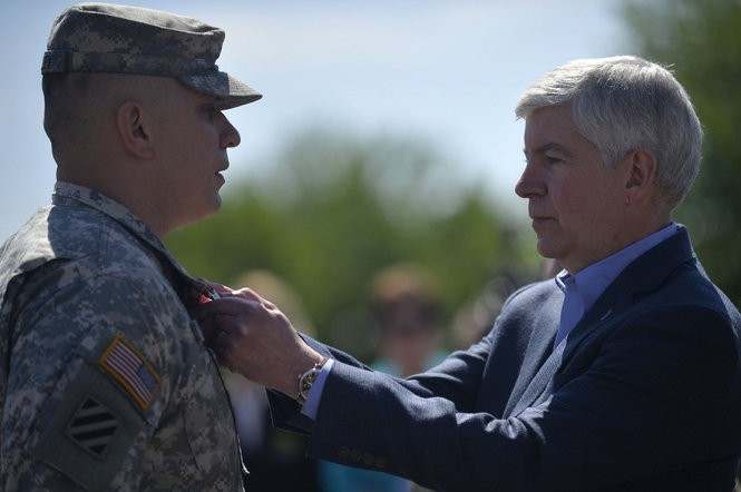 Gov. Rick Snyder puts a merit medal on a member of the National Guard after a press conference thanking and honoring the Michigan National Guard for their work during the Flint water crisis on Friday, May 20, 2016 at Dort Federal Credit Union Event Center in Flint. The press conference announced that the National Guard will wrap up Flint water operations by the end of May. Rachel Woolf | MLive.com