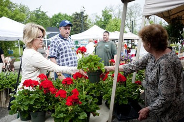 Joseph Tobianski   The Flint Journal Keri Pahl of Grand Blanc, left, buys geraniums from Sue Myer, right, from Myers Farm in North Branch at the Grand Blanc Farmers Market in this Flint Journal file photo.