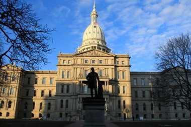 The statue of Gov. Austin Blair, the war governor (1861- 1864), is silhouetted against the state Capitol in Lansing, Mich., Wednesday, Dec. 12, 2012, a day after thousands of protesters rallied on the grounds as lawmakers pushed final versions of right-to-work legislation.
