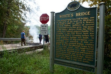 Residents of Ionia County look out at what's left of White Bridge after it burned down in an arson fire on Sunday, July 7, 2013. The historic bridge was Michigan's oldest original-construction covered bridge built in the late 1860s.
