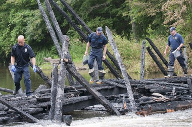 From left, Ionia Public Safety Sgt. Cory McDiarmid, Michigan State Trooper Mike Bush and MSP fire investigator Det. Sgt. Trevor Slater look for the cause of the fire that destroyed the historic Whites Bridge in Ionia County Sunday. Photo shot Monday, July 8, 2013.