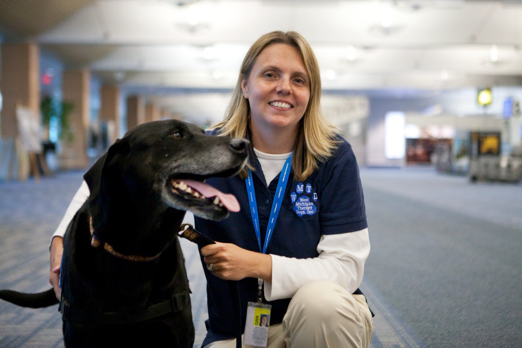 Amy Meinecke poses with Gunner, her 10-year old Black Lab, at Gerald R. Ford International Airport on Monday, October 8, 2013. The airport is launching a new therapy dog program to help take the stress and anxiety out of travel.