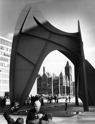 Sculptor Alexander Calder talks with attendees at the Calder sculpture dedication ceremony on June 14, 1969. The artist and his work are seen here with old city hall in the background.