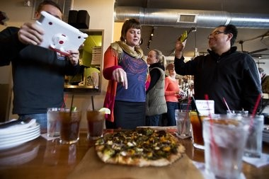 Co-owner of Harmony Brewing Company Heather VanDyke-Titus, center, speaks to MLive's Todd Chance, left, and John Gonzalez about the Harvest Moon pizza during day seven of Gonzalez's search for Michigan's best pizza in Grand Rapids on Saturday, November 16, 2013. (Andrew Kuhn   MLive.com)