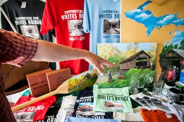 Keith Salter shows commemorative White's Bridge shirts at his home in Ionia, Mich., on Wednesday, June 25, 2014. The Supporters for Whites Bridge group is selling memorabilia in an effort to raise money to help rebuild the bridge.