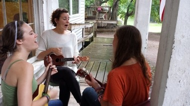 Holding an impromptu song session on the farmhouse porch are (from left): Malory Meletic, a camper from Grand Rapids; Rachel Varley, a counselor from Aquinas College; and Annalise Nordgren, a camper from Wisconsin. They are playing a song Varley wrote.