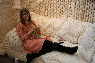 """Grand Rapids artist Annie """"Belle"""" Eckrich knits while greeting ArtPrize-goers who visit the house she knitted out of more than 400 pounds of wool roving. The entry, titled """"Woolhouse,"""" is on display at the Urban Institute for Contemporary Arts."""
