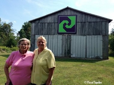 """Donna Sue Groves (right) with her mother, Nina Maxine Groves in front of the barn on their property. Nina Maxine, an avid quilter, inspired Donna Sue to start a trail of painted quilt squares in Adams County, Ohio in 2001. Now there are more than 400 trails in 40 states. The square on Groves family barn is a """"Snail's Trail"""" design."""