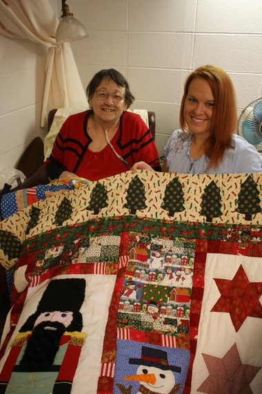 Jane Brooks (left) poses with the holiday themed quilt she stitched by hand with ironing assistance from Heather Hills Care Center staffer Amanda Hughey (right). The pair have teamed up for several quilting projects since Jane moved to the facility.