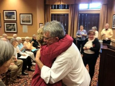 """Tim England, right, gets a hug from Beacon Hill retirement home resident Carol Garey after receiving an award for """"his courageous act of good citizenship"""" for confronting a pair of gun-carrying men at a Dec. 18 Grand Rapids City Commission meeting."""