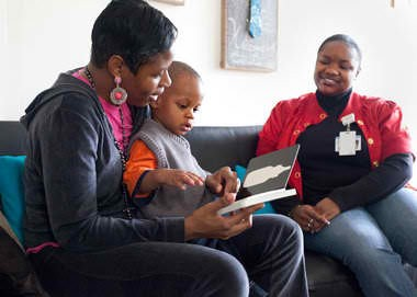Shardaira Johnson-Moore,of Grand Rapids, reads with her son, Naesean, 1, in her living room in March 2012 as Spectrum Community Health parent coach Keturah Bell observed. Johnson-Moore participated in the Believe 2 Become Baby Scholars program, which provides free help and educational support for families.