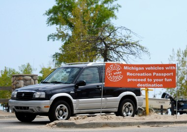 A car drives past a sign informing people about Michigan's Recreation Passport at the entrance to Grand Haven State Park in May 2011. The price of the passports has gone up to $11 this year, and the state Department of Natural Resources director wants to make a couple other changes, too.