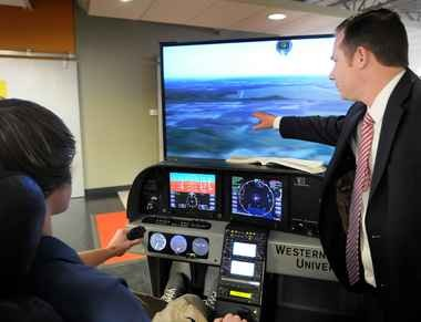 Lennox Ramsey, a West Michigan Aviation Academy student, tried out a new flight simulator in 2011 with help from aviation Instructor, Keith Sutherland. The $50,000 simulator was donated from Western Michigan University.