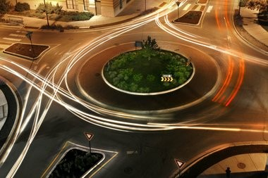 A time-exposure captures movement of vehicles traveling through a roundabout at Jefferson Avenue and Cherry Street SE in Grand Rapids. The city plans to install four roundabouts on Monroe Avenue NW in 2014.