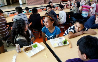 From left, Stefany Velasquez, Tazeana Edwards, and Juan Gonzalez, all of Grand Rapids, eat lunch in the cafeteria at Sibley Elementary on March 22, 2012. Sibley is a member of Kent Schools Social Network, a program that places multiple services in school buildings to help remove barriers to student achievement, including social workers and health care.