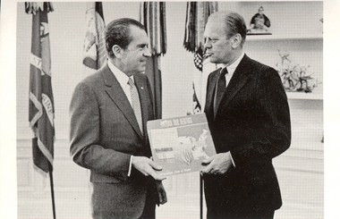 Then-Congressman Gerald Ford hands President Richard M. Nixon an album of songs from the Metropolitan Choir of Praise from Grand Rapids.