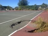 Part of a tennis court at Campau Park has caved in.