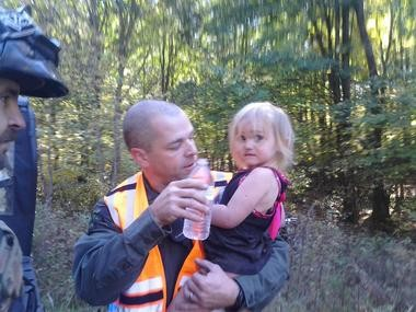 Department of Natural Resources Conservation Officer Jeff Ginn holds 2-year-old Amber Rose Smith moments after she was found in northern Newaygo County woods on Wednesday, Oct. 9