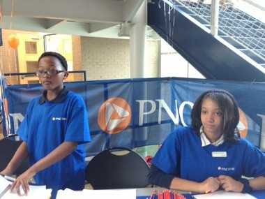 (From L to R) Alyssa Sallie, 10, and DeUnique Dorris, 12, are among 11 Martin Luther King Leadership Academy students working in the new, in-school, PNC bank. Students serve as bank tellers or marketers. The bank launched Wednesday, Oct. 30, at the school located at 645 Logan St. SE.