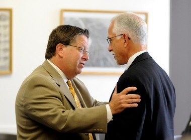 Grand Rapids City Manager Greg Sundstrom, left, talks in 2010 with his right-hand man, Deputy City Manager Eric DeLong. City Commission has reinstated 5-percent step increases in Sundstrom's pay scale.