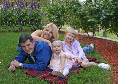 Chad Miller with Erica Sevigny and her two daughters, Madison, 2, and Emily, 7.