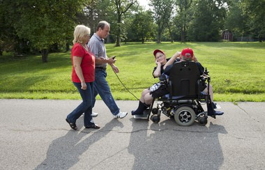 Donnie and Ronnie Galyon ride in their wheelchair in their Beavercreek, Ohio, neighborhood, while their brother Jim and his wife, Mary, use a joystick to control the wheelchair on Saturday, June 28, 2014. Donnie and Ronnie, born Oct. 28, 1951, are the world's oldest living conjoined twins.