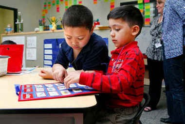 In this file photo, Sibley Elementary first-graders Jaylin Garcia, left, and Mauricio Ramirez, play an academic game. Sibley is a member of Kent Schools Social Network. The state, in part, modeled its Pathways to Potential program after the Kent Schools Social Network.