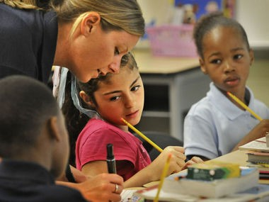 Fourth grade teacher Nicole Titus works with students Isise Elmer and Promise Walker, right, at Dickinson Elementary on August 9, 2012.