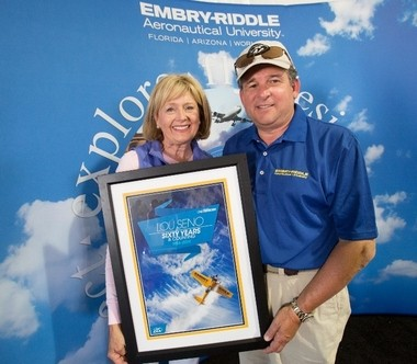 Louis Seno Jr., vice president of corporate relations and government affairs at Embry-Riddle Aeronautical Universty and his wife, Christine, hold his recent award for 60 consecutive years of attending Experimental Aircraft Association conventions. The couple announced it pledged $150,000 in scholarship support to West Michigan Aviation Academy for graduates attending Embry-Riddle on Thursday, Dec. 4, 2014. They also donated his late father's Corben Junior Ace aircraft for display.