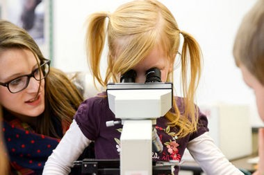 Evergreen Christian Elementary school student Brynn VanDrie looks at a strand of hair through a microscope to learn about cells using a curriculum designed by Calvin biology professor Amy Wilstermann to help young children learn about cancer on Thursday, January 15, 2015. (Emily Rose Bennett | MLive.com)