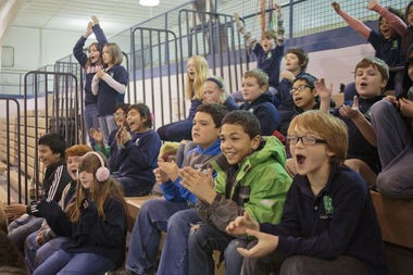 Fifth graders from West Michigan Academy of Environmental Science cheer as players from the Grand Rapid Drive help them conduct science experiments on November 12, 2014.