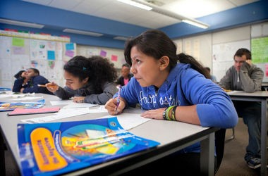 Casandra Madero, 12, on right, and Princess Leon, 12, take notes in their seventh grade math class at Alger Middle School on Monday, October 28, 2013. Alger is one of five schools recommended for Teach for America instructors.