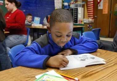 Mark Dolo, 7, of Wyoming reads in his first grade class at North Godwin Elementary on Jan. 11, 2011, during backpack reading time. North Godwin is one of five West Michigan schools involved in a Reading Now Network