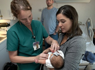Nurse Hannah Charity places an oxygen monitoring sensor on Hillary Smith's newborn Charlotte. The screening test looks for signs of critical congenital heart disease. Photo taken at Mercy Health St. Mary's in Grand Rapids, Mich. Tuesday, October 8, 2013. (Chris Clark | MLive.com)