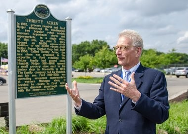 Hank Meijer stands next to the Michigan Historical Marker on the site of the retailer's original Thrifty Acres store.