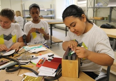Photo of three of the 60 sixth-graders attending the new Grand Rapids Public Museum School this year. The Grand Rapids Public Schools students attended a three-day orientation. The photo is of some students at the Kendall College of Art and Design creating prototypes of the letterbox project they were assigned.