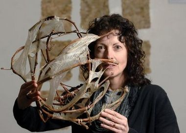 """Jo-Ann VanReeuwyk holds a piece of art she created called """"Sheath, """" which she made from grapevine and is displaying during a Calvin Symposium on Worship in 2010."""
