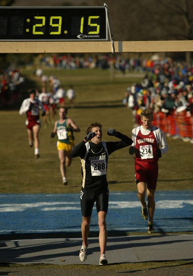 Dathan Ritzenhein, while at the University of Colorado, celebrates as he crosses the finish line to win the 10,000-meter race at the NCAA cross country championships in Waterloo, Iowa in 2003.