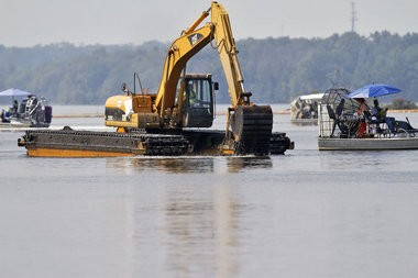 In this file photo, an excavator digs into the bottom of Morrow Lake as cleanup continues following the 2010 Enbridge oil spill into the Kalamazoo River. (Kalamazoo Gazette / Jonathon Gruenke)