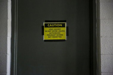 A lead hazard sign is posted on the boiler room door at the Grand Valley Armory on Friday, Dec. 2, 2016 in Wyoming, Mich. (Chelsea Purgahn/Kalamazoo Gazette)