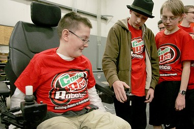 From left, Grandville resident Nevin Hooper, 12, learns the controls of his new all-terrain wheelchair with help from Chad Ries, 13, and Luke Orzechowski, 14, both of Grandville.