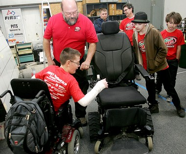 Nevin Hooper, 12, of Grandville, checks out his new all-terrain chair with Code Red team coach Ken Orzechowski, of Grandville, at the team's build space in Kentwood.