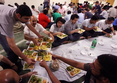 Gathered for an iftar: Fahad Minhaj distributes a tray full of meals at the Kalamazoo Islamic Center as congregants gather after sunset Sunday evening for a meal called an iftar, in this file photo. Men ate in one room, and women and children in another.
