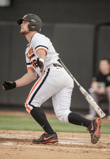 Oklahoma State junior right fielder Zach Fish watches the ball fly off of his bat during a game against Oakland University on Feb. 22. The Kalamazoo native on Tuesday was named the Big 12 Player of the Year.