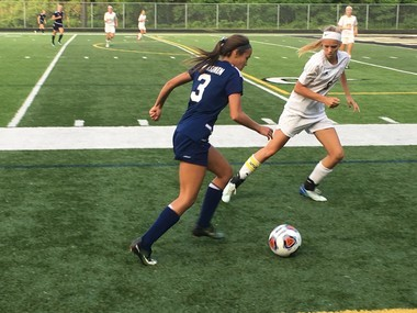 North Muskegon's Megan Sroka (3) tries to advance the ball upfield against the defense of Kalamazoo Christian's Carmen Katje during a Division 4 state semifinal match Tuesday, June 12, 2018 at Comstock Park High School.