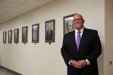 Rob Olsen, acting superintendent of Portage Public Schools, in the Portage Public Schools Administration Building. Behind Olsen are portraits of Portage's previous superintendents.
