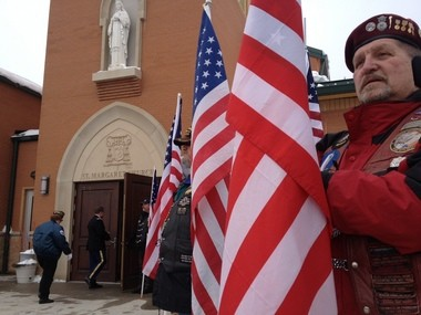 Bill Schwalm, of Saginaw, a member of the Patriot Guard Riders, stands outside St. Margaret Catholic Church in Otsego.